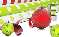 rolls of gift wrapping paper and ribbon with red and green christmas baubles - stock photo