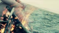 Man sitting on the beach near a campfire - stock footage
