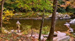 Elderly fly fisherman casting line autumn Stock Footage