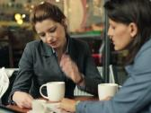 Young businesswomen with newspaper in cafe, steadicam shot NTSC Stock Footage