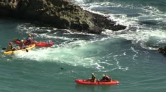 Yellow and red canoes near rocks in the sea Stock Footage