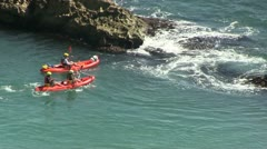 Red  canoes  near rocks in the sea - stock footage