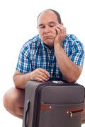 bored traveller man with luggage - stock photo