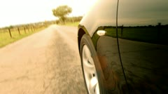 Black car on the country road - focus on spinning front wheel Stock Footage