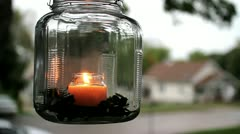 Close up of hanging candle on front porch with house in background Stock Footage