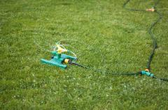 lawn sprinkler over green grass - stock photo
