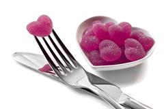 pink heart shaped jelly sweets with knife and fork on white - stock photo