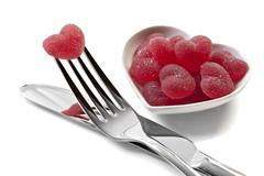 red heart shaped jelly sweets with knife and fork on white - stock photo