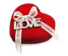 A red heart with the word love spelled out in silver Stock Photos