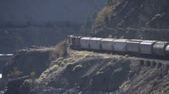 Freight train on canyon wall s-turn longshot, backlit Stock Footage