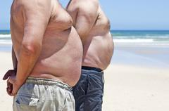 close up of two obese fat men of the beach - stock photo