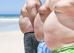 close up of three obese fat men of the beach - stock photo