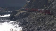 Railroad, freight train on canyon wall s-turn medium shot, backlit Stock Footage