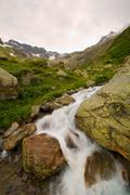 Stock Photo of Mini Waterfall A Furious River In Switzerland In Mountains