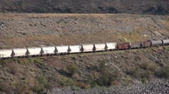 Railroad, freight train mixed frieght along semi-arid valley long shot Stock Footage