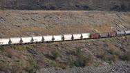 Railroad, freight train mixed frieght along semi-arid valley long shot Stock Footage