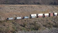 Railroad, freight train containers along semi-arid valley long shot Stock Footage