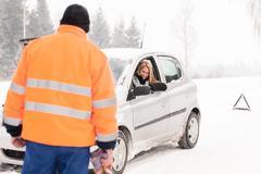 man helping woman car breakdown assistance snow - stock photo