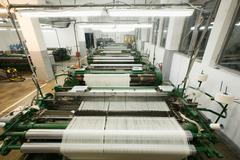 Weaving Machines Lined Up In Textile Factory Workshop Stock Photos