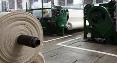 Textile Factory With Roll In Foreground And Machines In Background Stock Photos
