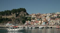 Tour boat arrives at parga harbour with town and castle in the background Stock Footage