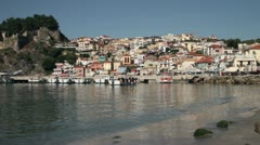 Waves lapping the shore as a tour boat leaves parga town, greece Stock Footage