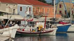 Fishing boats moored in front of tavernas at fiskeardo, kefalonia, greece Stock Footage