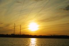 Sun setting behind electricity pylon Stock Photos