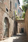 Little Italian street with bridge in Cortona. - stock photo