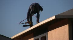 Home construction, air nailing roof, handheld Stock Footage