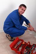 Plumber kneeling by tool box Stock Photos