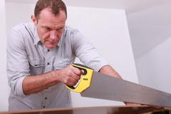 Handyman with hand saw Stock Photos