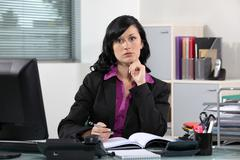 Brunette office worker thinking - stock photo