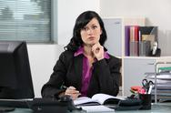 Stock Photo of Brunette office worker thinking