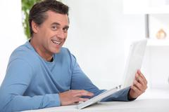 Man working at home via the internet - stock photo