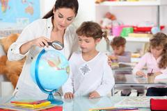 Stock Photo of teacher, pupil, reading, globe