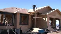 Home construction, air nailing roof wide shot, handheld Stock Footage
