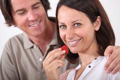man embracing his wife while she is eating strawberries - stock photo