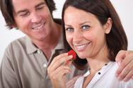 Stock Photo of man embracing his wife while she is eating strawberries