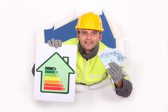Laborer with energy rating sign and bills in hands Stock Photos