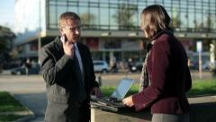 Business people with laptop and cellphone in the city, steadicam shot HD Stock Footage