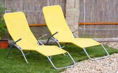 Stock Photo of two empty yellow sun loungers on a garden