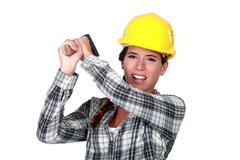 Craftswoman striking with a hammer Stock Photos