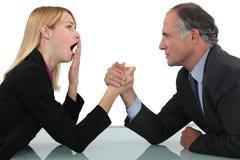 Woman arm wrestling with her boss - stock photo
