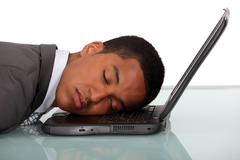 Young businessman asleep on laptop Stock Photos