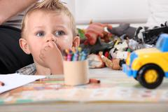 Little boy drawing with crayons - stock photo