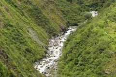 Stock Photo of Small River Crossing Green Slopes Of Andes Mountains South America