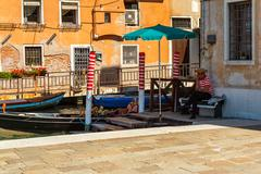 16. jul 2012 - gondolier waiting for tourists at canal in venice, italy - stock photo