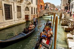 16. jul 2012 - gondoliers with tourists at canal in venice, italy - stock photo