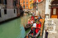 Stock Photo of 16. jul 2012 - gondolier with tourists at canal in venice, italy